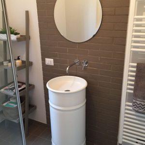 Lavabo freestanding e specchio tondo su parete grigia davanti